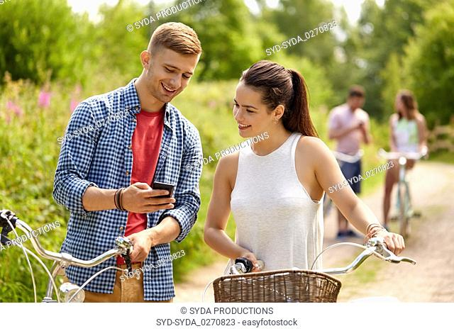 couple with smartphone and bicycles in summer
