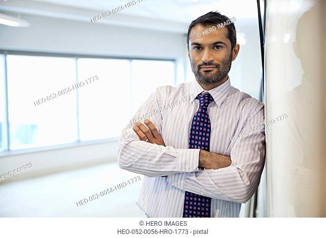 Portrait of businessman with arms crossed leaning on wall