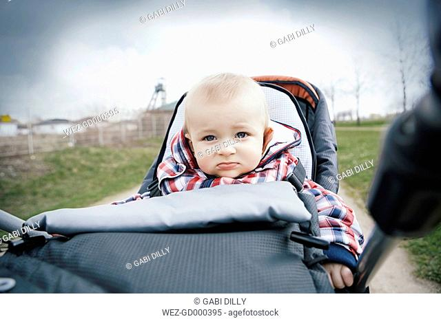 Germany, Oberhausen, Blond baby boy sitting in pram