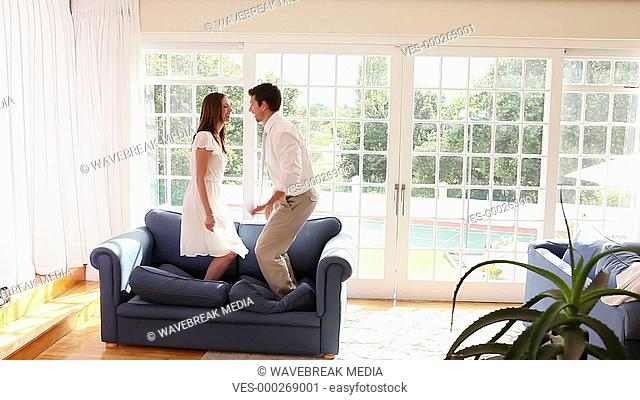 Happy couple jumping on the sofa
