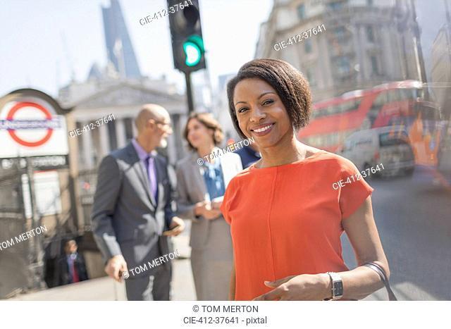 Portrait smiling businesswoman on sunny urban city street, London, UK