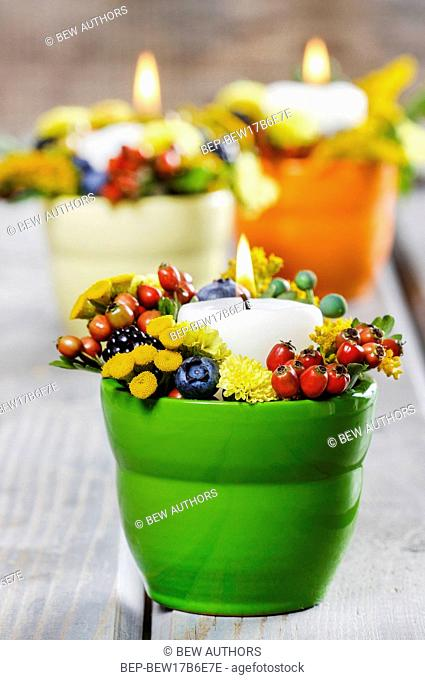 Candle holder decorated with autumn flowers and other plants. Selective focus
