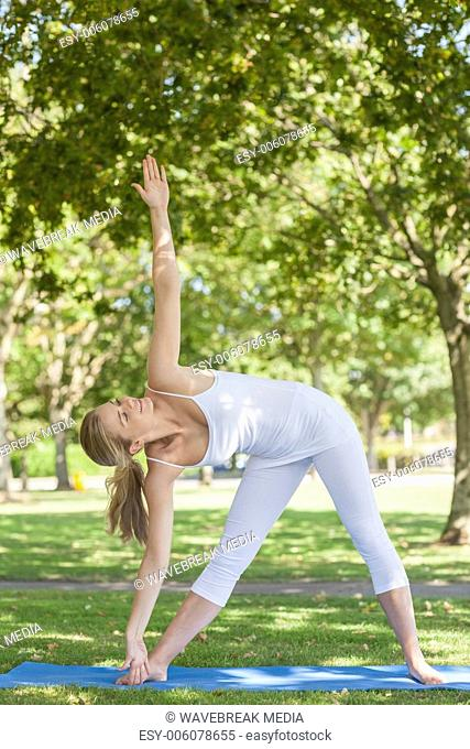 Young fit woman stretching her body with yoga pose