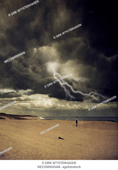 France, Contis-Plage, man standing at beach, thunderstorm and lightning, digitally manipulated