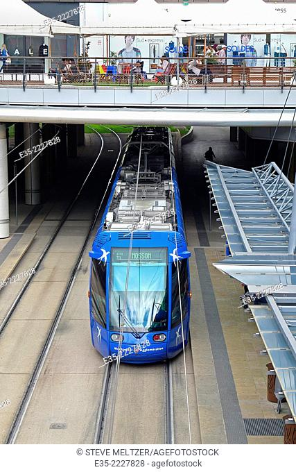 A tram pulls inot a train station at a shopping mall