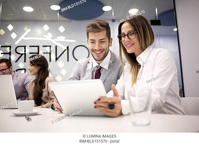 Caucasian business people using digital tablet in office meeting