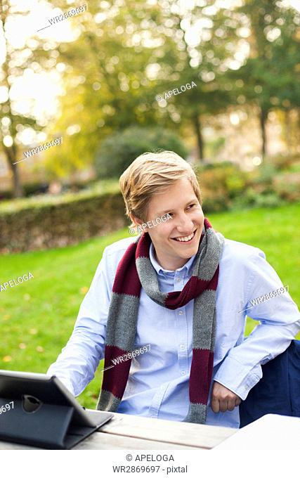 Happy handsome man sitting at table with digital tablet in campus