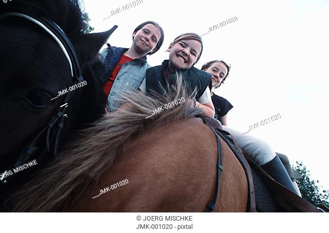 Three girls riding horses, sitting in the saddle, smiling