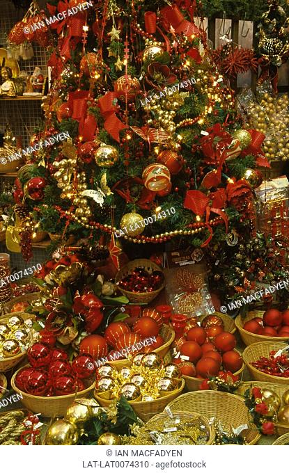 Artificial Christmas tree. Decorated with tinsel/ glass balls. Red/ gold colours
