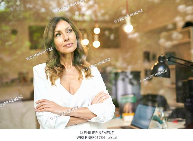 Business woman with crossed arms behind window