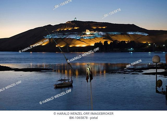 Nile at dusk, Qubbet el Hawa rock mountain with illuminated rock cut graves in the back, Aswan, Egypt, Africa