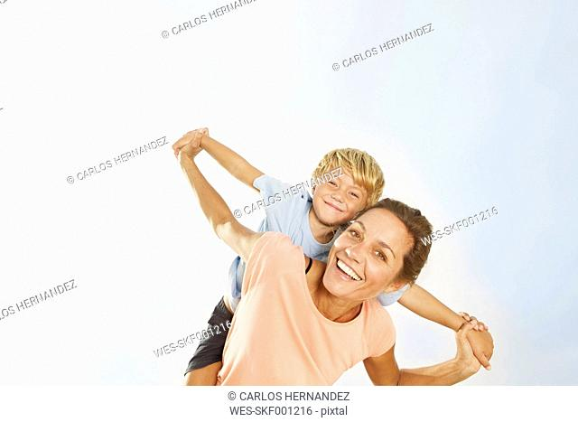 Spain, Mother giving piggy back ride to son, smiling