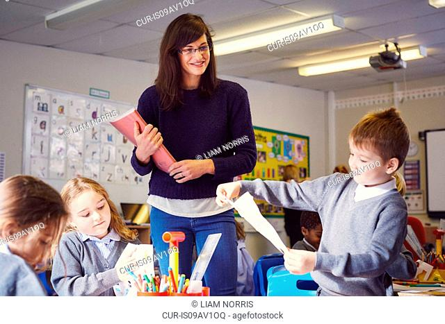 Female teacher with children drawing in elementary school classroom