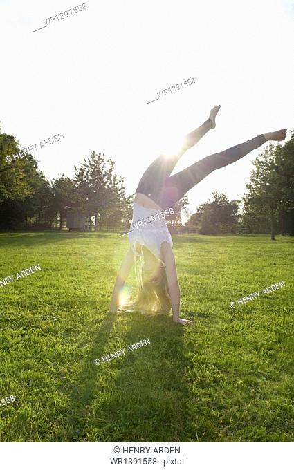 Teenage girl with long blond hair doing a headstand