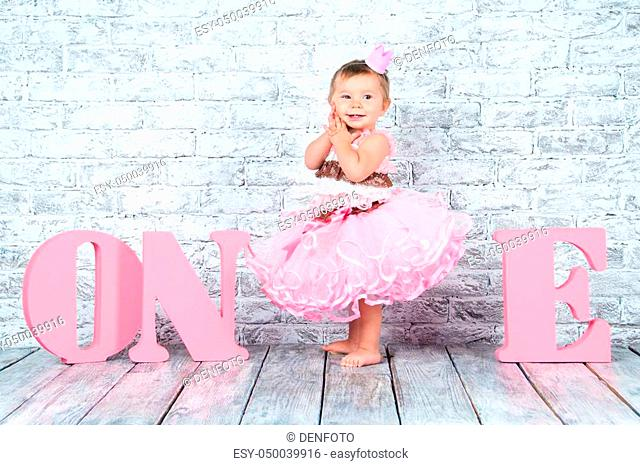 Beautiful and cute girl in a pink dress with the letters one on her first birthday. Emotional girl