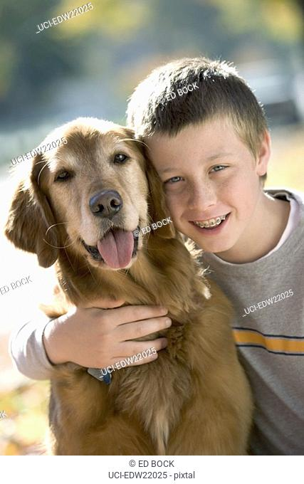 Boy with braces smiling and hugging his dog