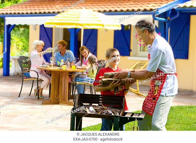 Multi-generational family barbecuing on patio