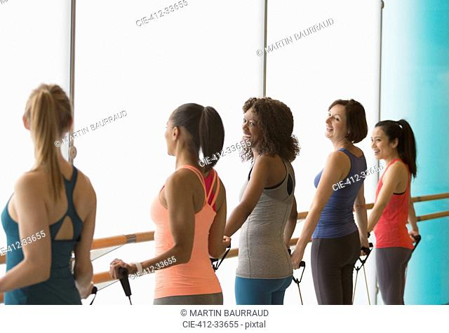 Smiling women exercising with resistance bands in gym studio
