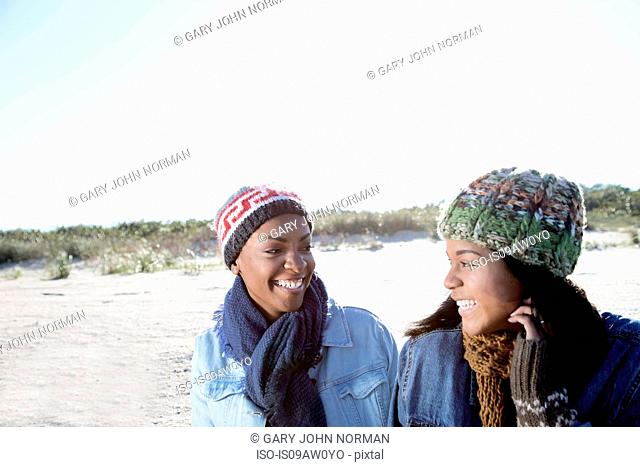 Two female friends relaxing at beach in winter