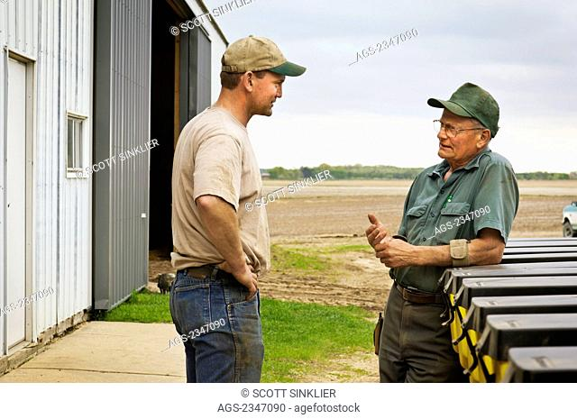 Agriculture - Father and son farmers discuss Spring planting operations on their farm / Central Iowa, USA