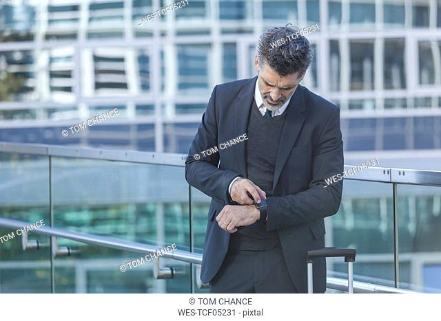 Businessman standing on bridge checking the time
