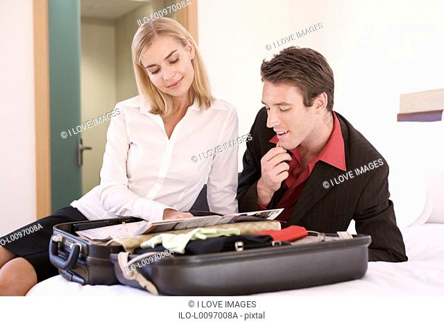 A couple reading a brochure on a open suitcase