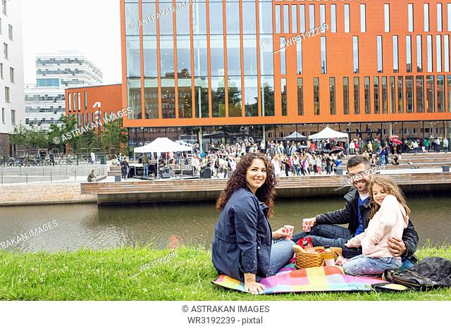 Portrait of parents with daughter (4-5) enjoying picnic with concert in background