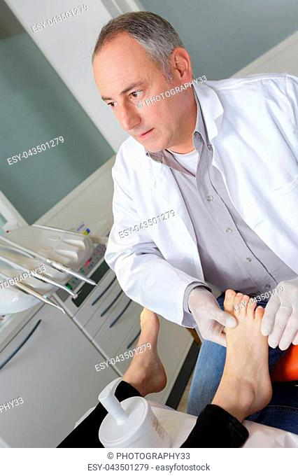 woman receives foot examination from gloved podiatrist