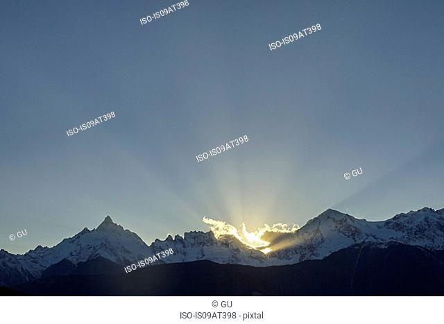 Sunbeams behind snow capped mountains, Shangri-la County, Yunnan, China