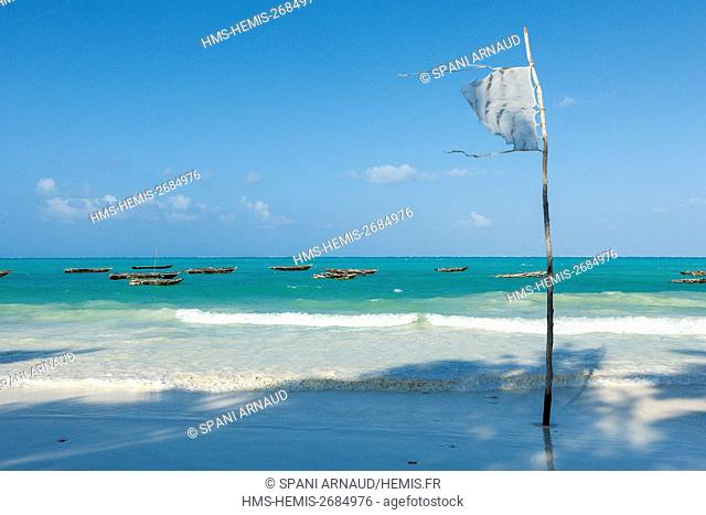 Tanzania, Zanzibar, Jambiani, flag flying on the beach beside a lagoon