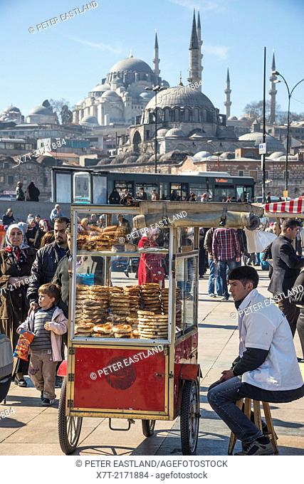 Simit bread vendor on the quay at Eminonu by Galata bridge, with the Suleymaniye & Yeni mosques in the background. Istanbul, Turkey