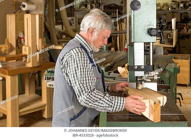 Wooden mask carver cutting a wooden block using a band saw, Bad Aussee, Styria, Austria