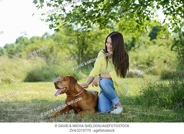 Close-up of a Woman with a Hungarian or Magyar Vizsla (Vizsla) on a meadow in spring