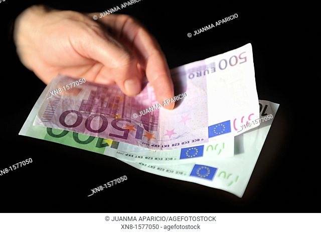 A hand on a black background with a five-hundred and one hundred euros