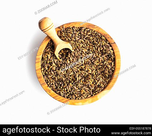 Milk thistle seeds in wooden bowl isolated on white background