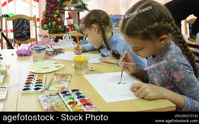 Two girls draw at their desks in the drawing lesson