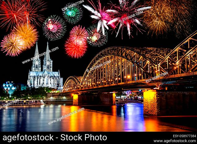 Night with fireworks in Cologne at the river Rhine with the illuminated cathedral and the Hohenzollern Bridge