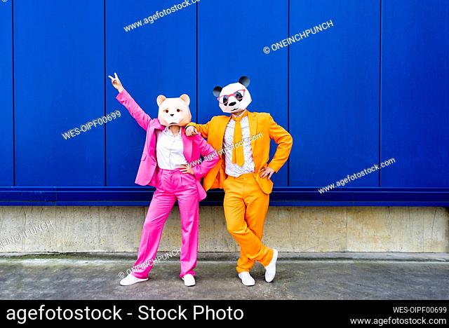 Man and woman wearing vibrant suits and bear masks standing together against blue wall