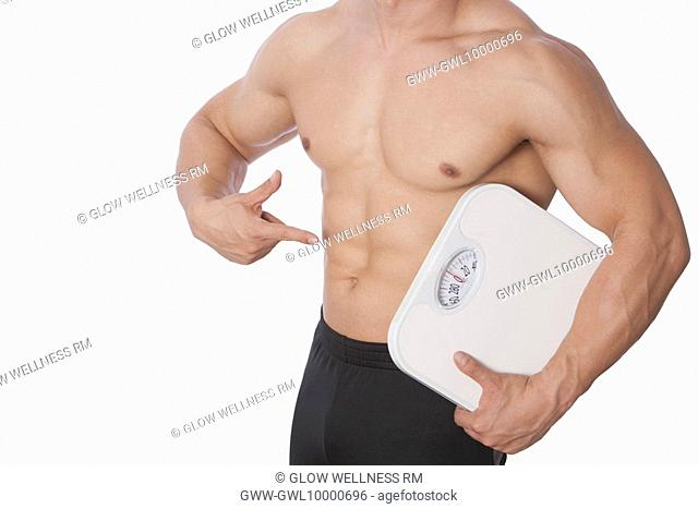 Mid section view of a man holding a bathroom scale and showing his abdomen