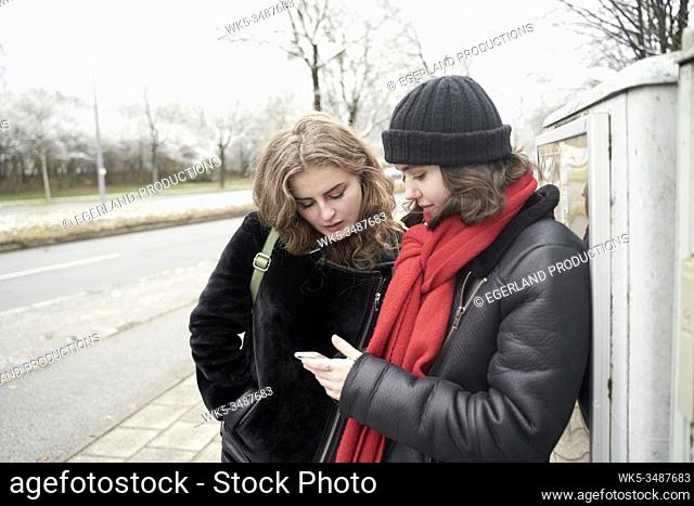 friends using smartphone at street