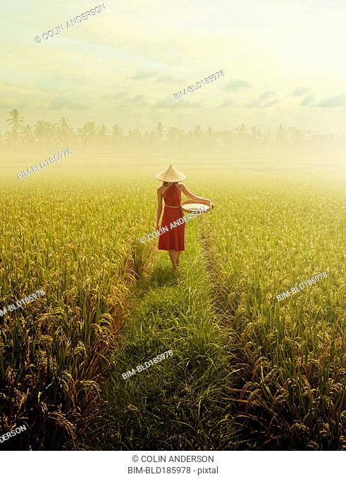 Pacific Islander woman walking in rice field