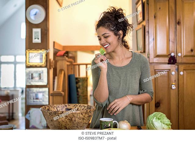 Young woman preparing salad at kitchen counter eating lettuce