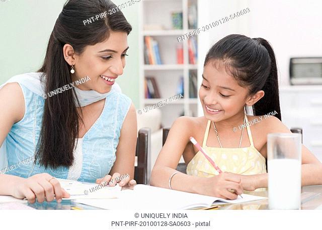 Woman helping her daughter in studies