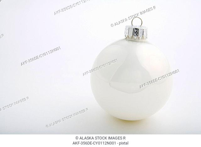 One white Christmas tree bulb ornament with silver hook on white background studio portrait