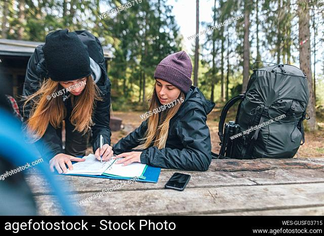 Young woman backpacking in Sweden, signing at camping ground
