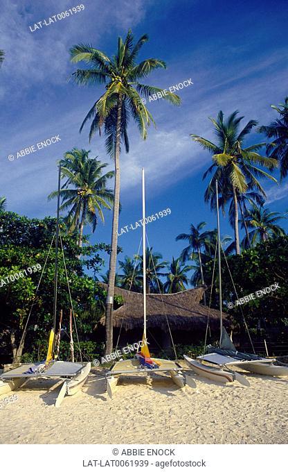 Visayas Islands. Tambuli Beach Resort. Thatched chalet/ accommodation. On beach. Catamaran sail boats