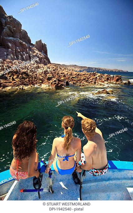 three tourists sitting on the edge of a boat with snorkeling gear at los islotes national marine park espiritu santo island, la paz baja california mexico