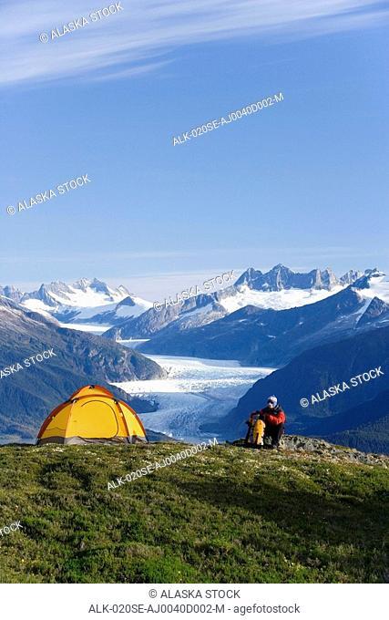Hiker next to tent on ridge views Mendenhall Glacier & Coast Mountains near Juneau Alaska during Summer