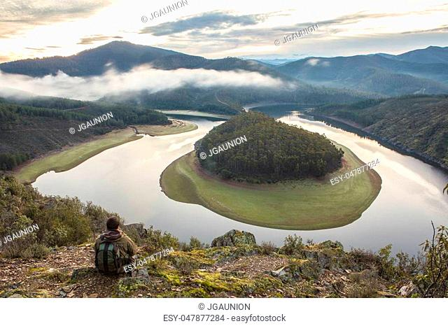 Tourist looks at Alagon River Meander with sunrise in the morning alone and active lifestyle. This place is called The Melero and is not far from Riomalo de...