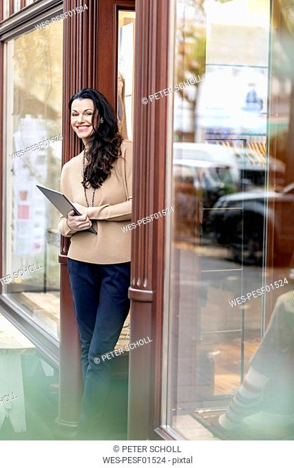 Mature woman standing in door of a fashion store, holding digital tablet